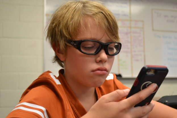 7th grade student spencer miller enjoys the outsiders by s.e. hinton. photo by zack catuogno