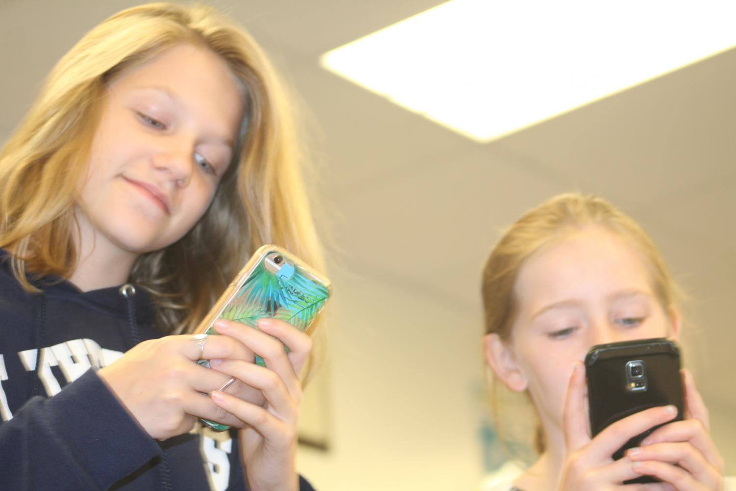 In this photo two girls (Emma Ross and Hannah McDonough) are texting instead of socializing with each other.
