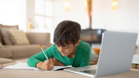 Front view of African american boy using laptop while drawing a sketch on book at home